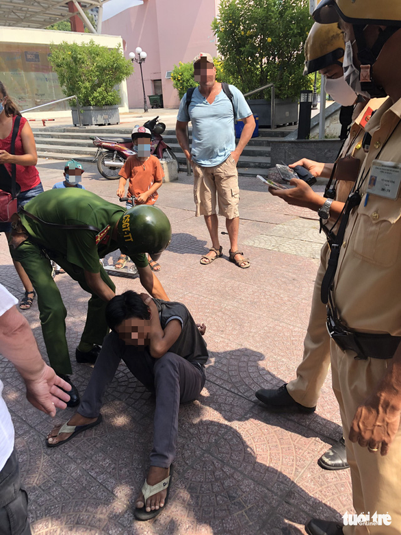 A police officer pins down T.Q.T. as another shows the phone he snatched from a French couple in District 1, Ho Chi Minh City, March 25, 2020. Photo: Tuoi Tre
