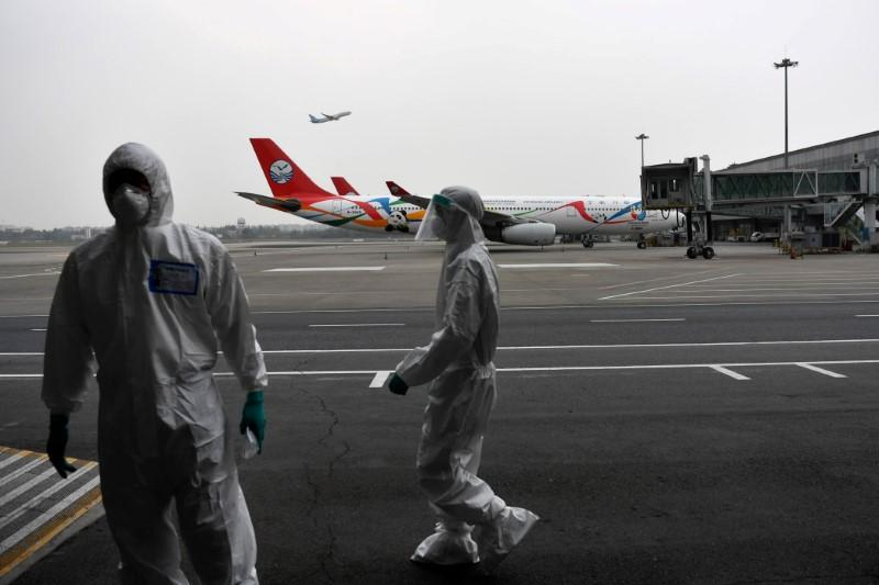 Customs officers in protective suits are seen near a Sichuan Airlines aircraft on the tarmac of Chengdu Shuangliu International Airport following a global outbreak of the coronavirus disease (COVID-19), in Chengdu, Sichuan province, China March 26, 2020. Photo: Reuters