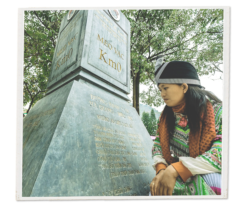 An ethnic woman views a milestone marking 'kilometer zero' of the Ha Giang Loop in Meo Vac District, Ha Giang Province, Vietnam.