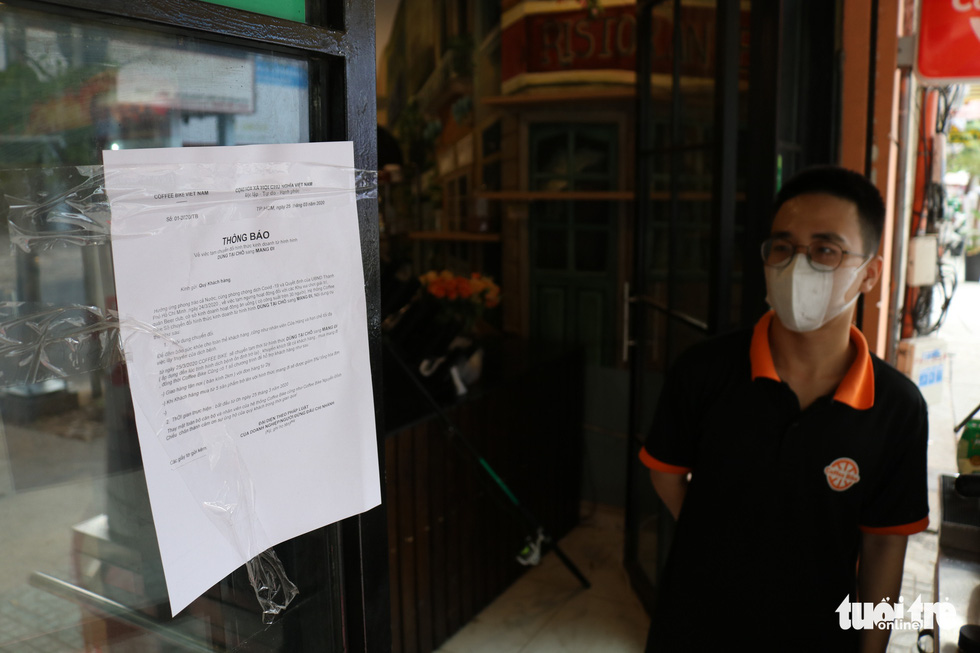 An employee looks at an announcement for 'takeaway service only' posted on the door of a coffee shop in District 1, Ho Chi Minh City, Vietnam, March 29, 2020. Photo: Ngoc Phuong / Tuoi Tre