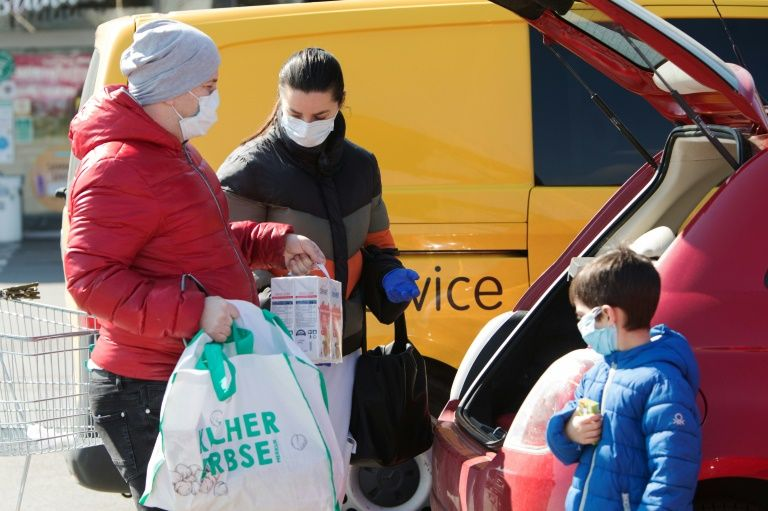 A family ensure they have their masks on as they put shopping in the car in Brunn am Gebirge near Vienna. Photo: AFP