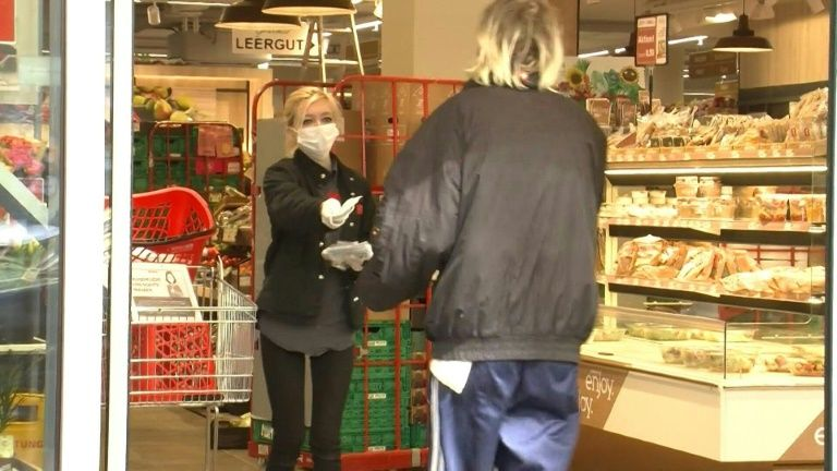 Supermarket employees hand out masks to customers as they enter, as Austria implements new rules compelling people to cover their faces in public places to slow the spread of coronavirus. Photo: AFP