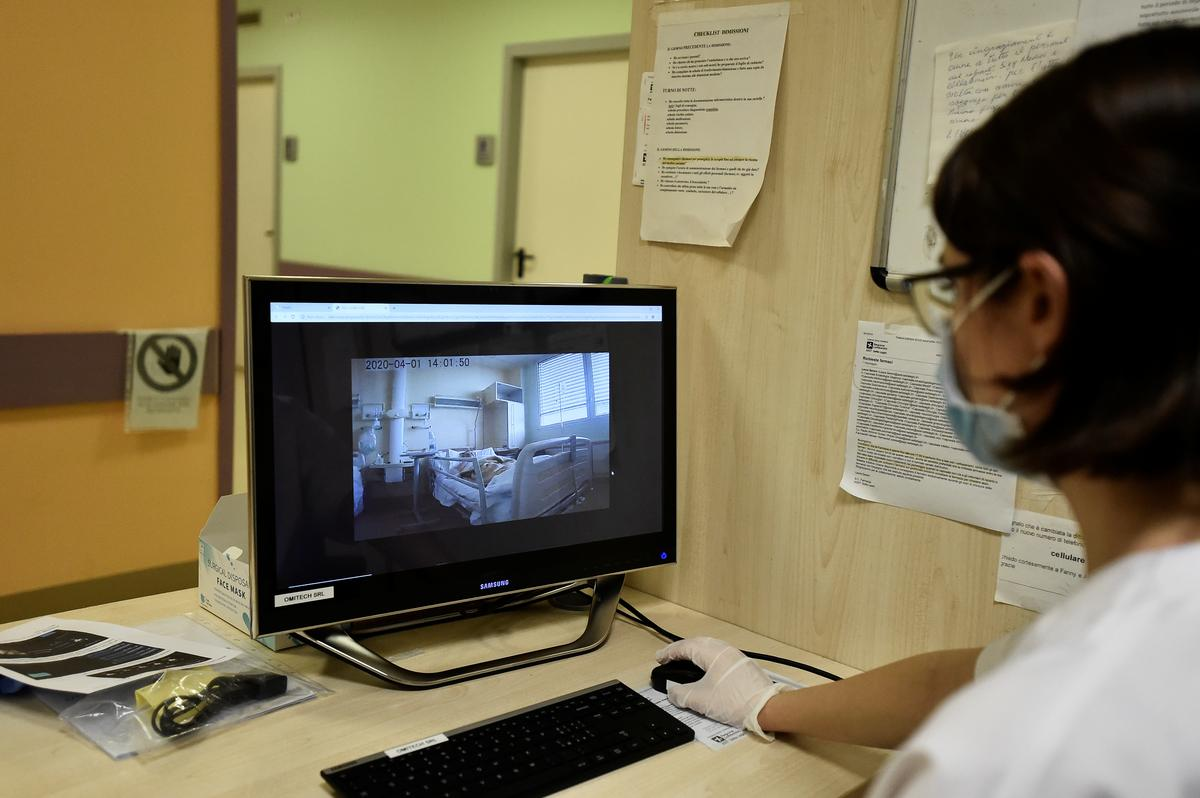 A health worker looks at the screen showing images taken by a robot helping medical teams treat patients suffering from the coronavirus disease (COVID-19), in the Circolo hospital, in Varese, Italy April 1, 2020. Photo: Reuters