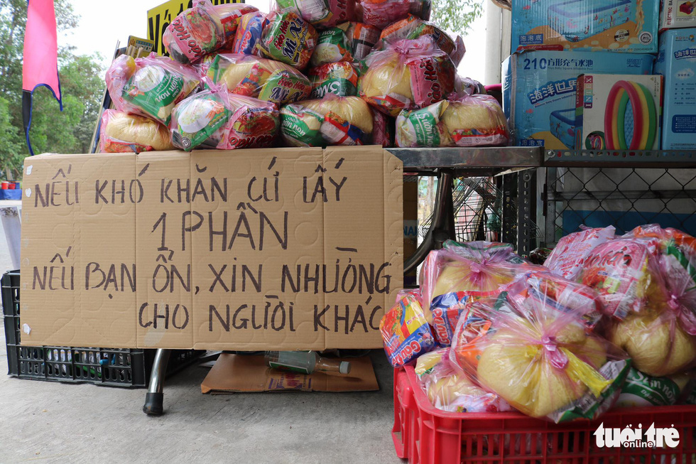 Gift bags with rice, noodles and other essential foods are prepared at a local's house in the southern province of Binh Duong for poor people to pick up. The sign reads 'If you are having a tough time, please take one. If you are fine, please leave some for others'. Phto: Ngoc Phuong/ Tuoi Tre