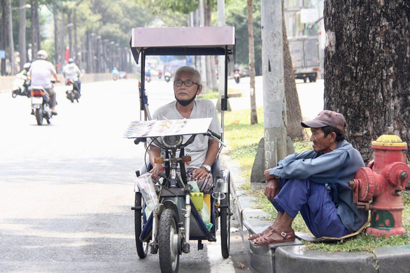 An old lottery ticket seller is seen on his hand-operated tricycle in this photo taken on a street in Ho Chi Minh City. Photo: Le Phan/ Tuoi Tre