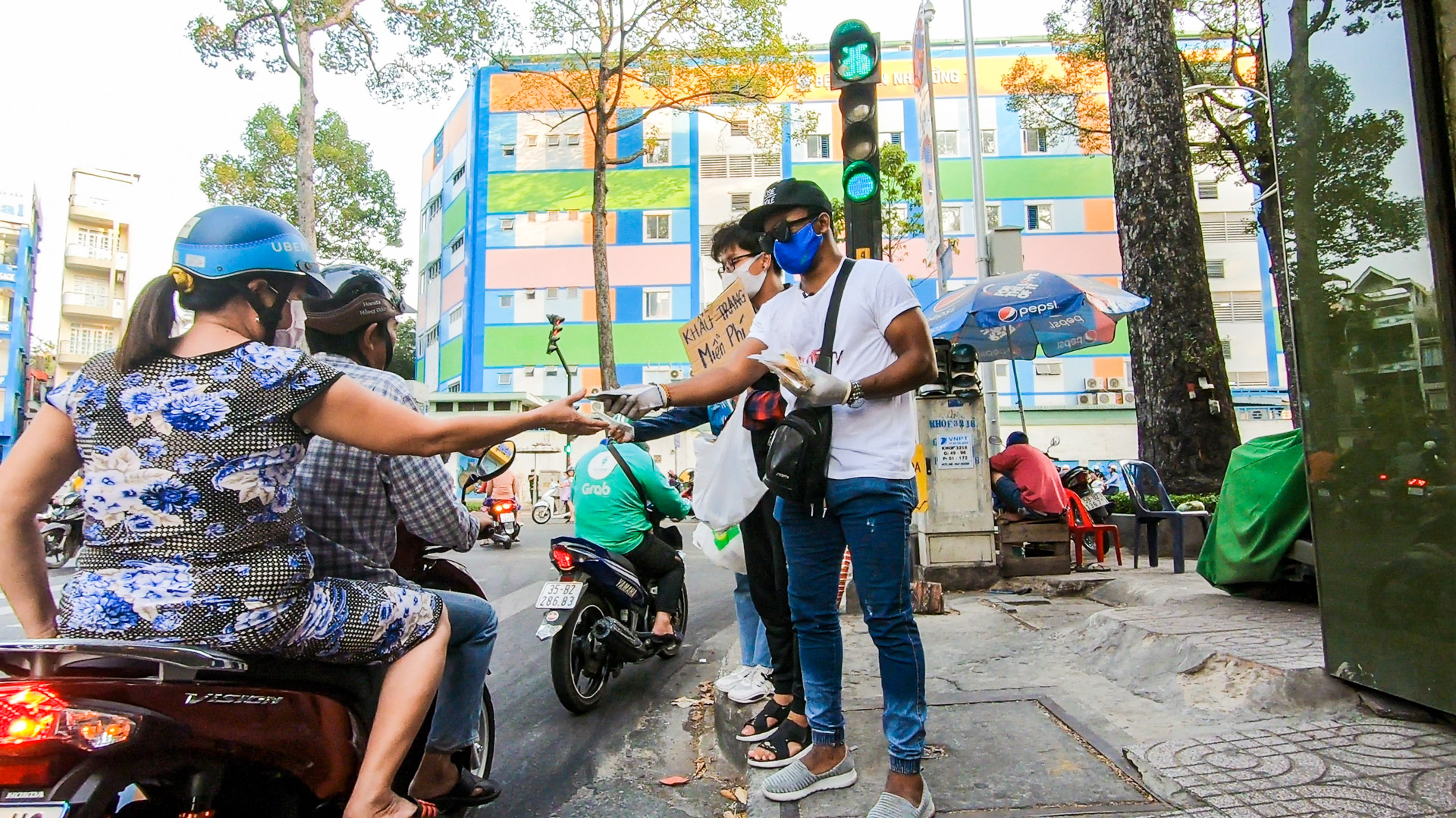 Nnadozie Uzor Nadis, a Nigerian YouTuber based in Ho Chi Minh City, delivers free face masks to locals on the streets of Ho Chi Minh City in this supplied photo.