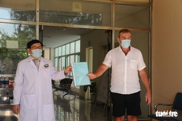 C.P.S. (R), a 66-year-old British COVID-19 patient, and a doctor hold a discharge certificate at Quang Nam Central General Hospital in Quang Nam Province, Vietnam, April 5, 2020. Photo: Le Trung / Tuoi Tre