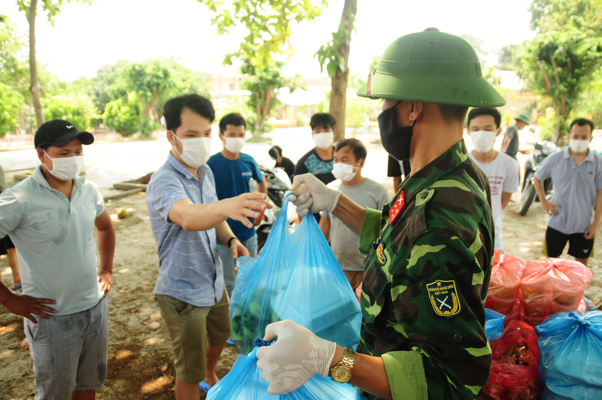 Boxes of steaming rice and food are handed to quarantined people at Hanoi Capital High Command's Military School in Hanoi, Vietnam. Photo: Nguyen Khanh / Tuoi Tre
