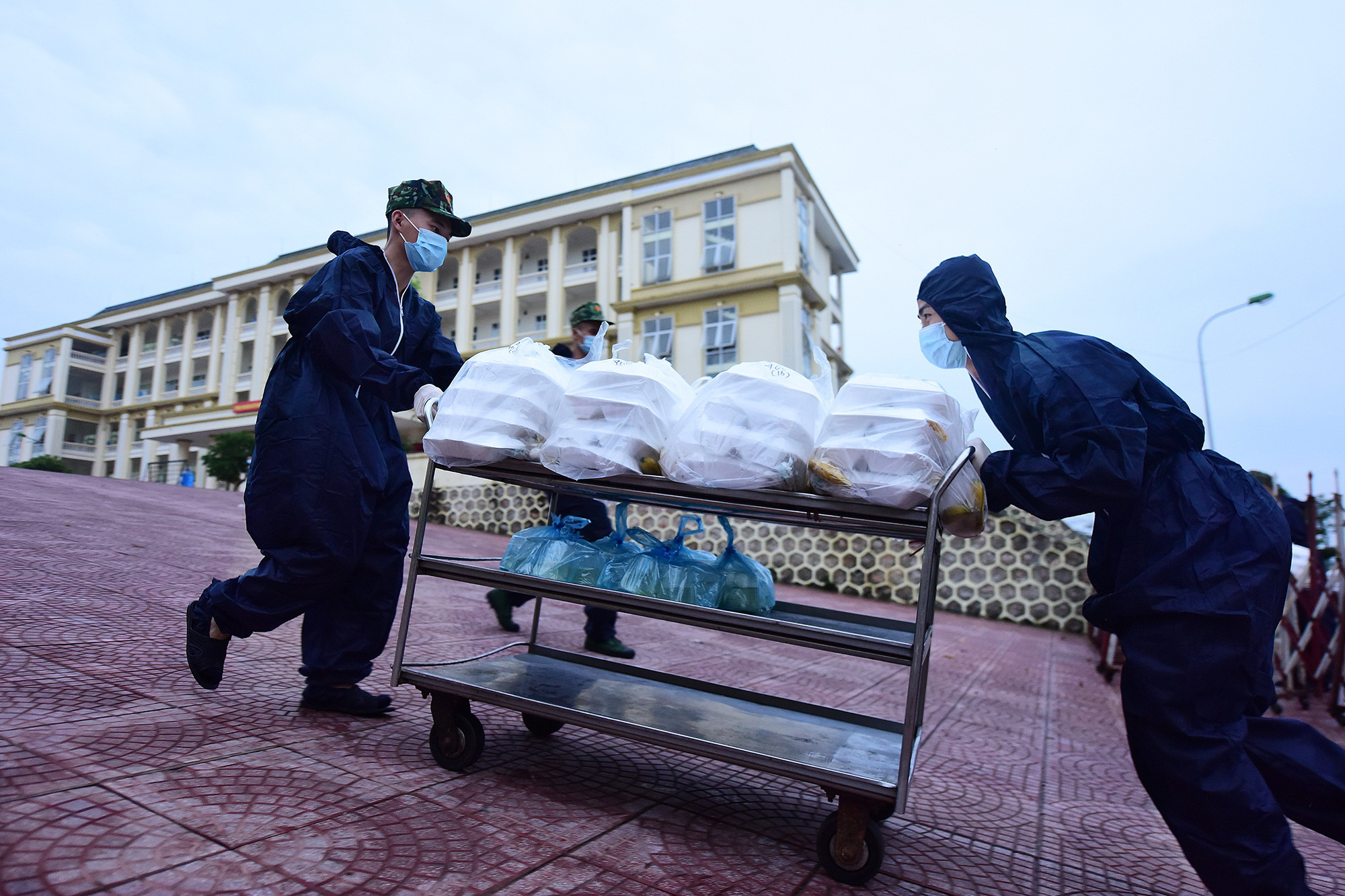Two soldiers are pushing a trolley topped with boxes of rice on their way to the quarantined zone in Vietnam. Photo: Nguyen Khanh / Tuoi Tre