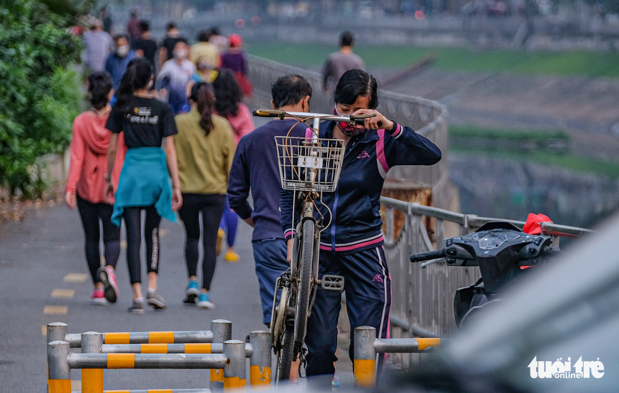 A woman lifts her bicycle over a barrier on a pedestrian lane of Lang Street along To Lich River in Hanoi, Vietnam in this photo taken in early April 2020. Photo: Nam Tran / Tuoi Tre