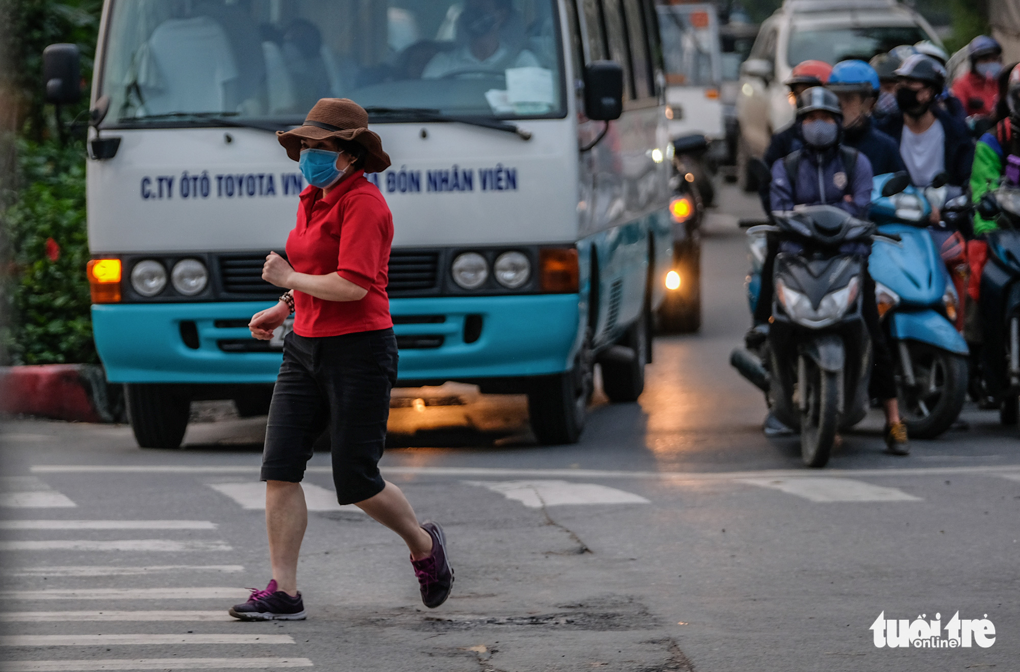 A woman crosses the road to get to a pedestrian lane of Lang Street along To Lich River in Hanoi, Vietnam in this photo taken in early April 2020. Photo: Nam Tran / Tuoi Tre