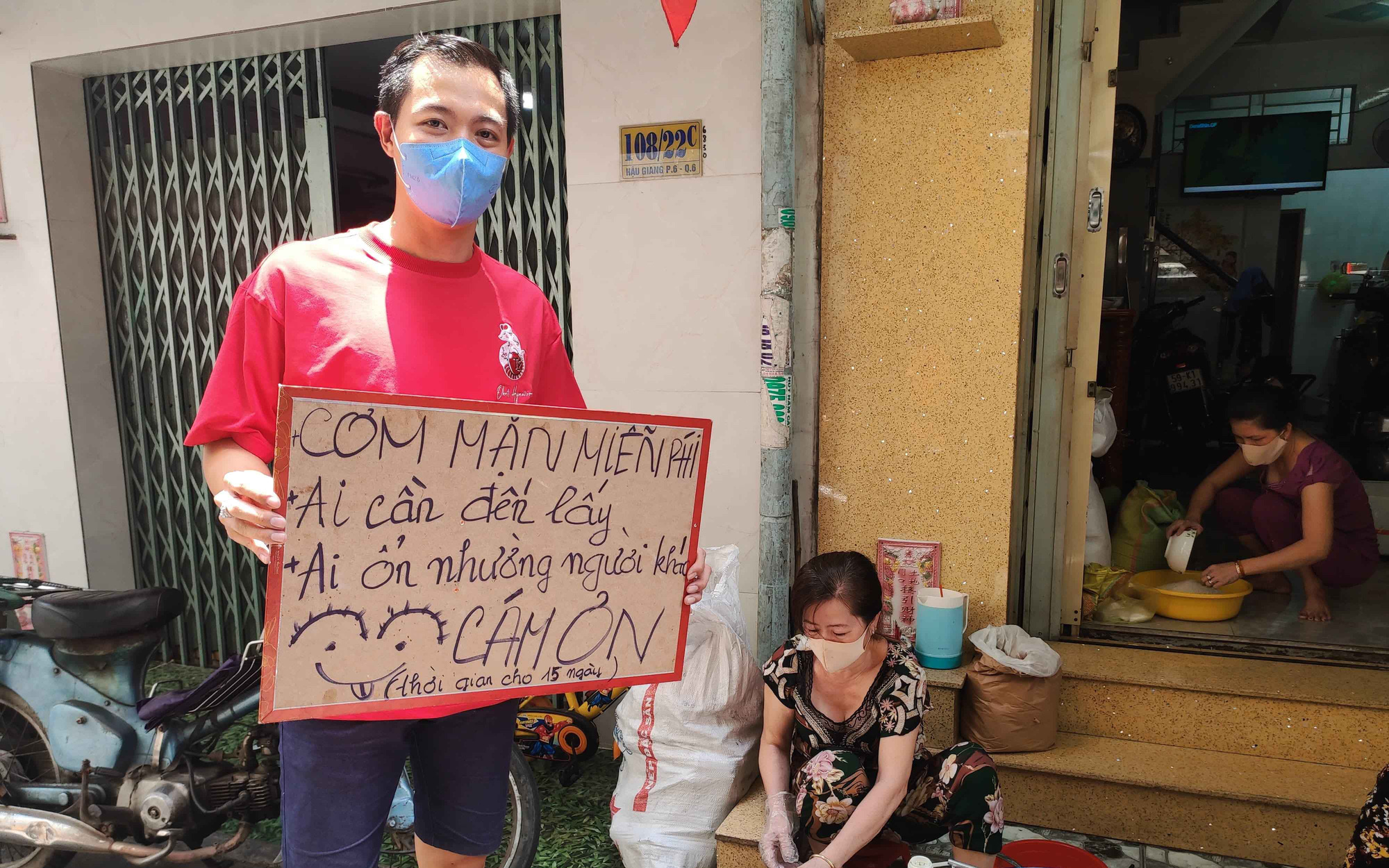Truong Nhat Hoang Quan and his relatives prepare free meals for the needy in District 6, Ho Chi Minh City, Vietnam. The sign he's holding reads, 'Free non-vegan meals. You can take one if [you are] in need. If you are doing fine, please leave it for others.' Photo: Minh Vu / Tuoi Tre