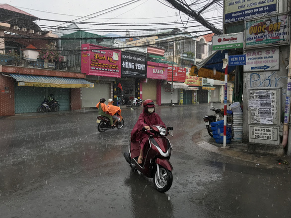People ride motorbikes in the rain in Tan Phu District, Ho Chi Minh City, April 9, 2020. Photo: Le Phan / Tuoi Tre
