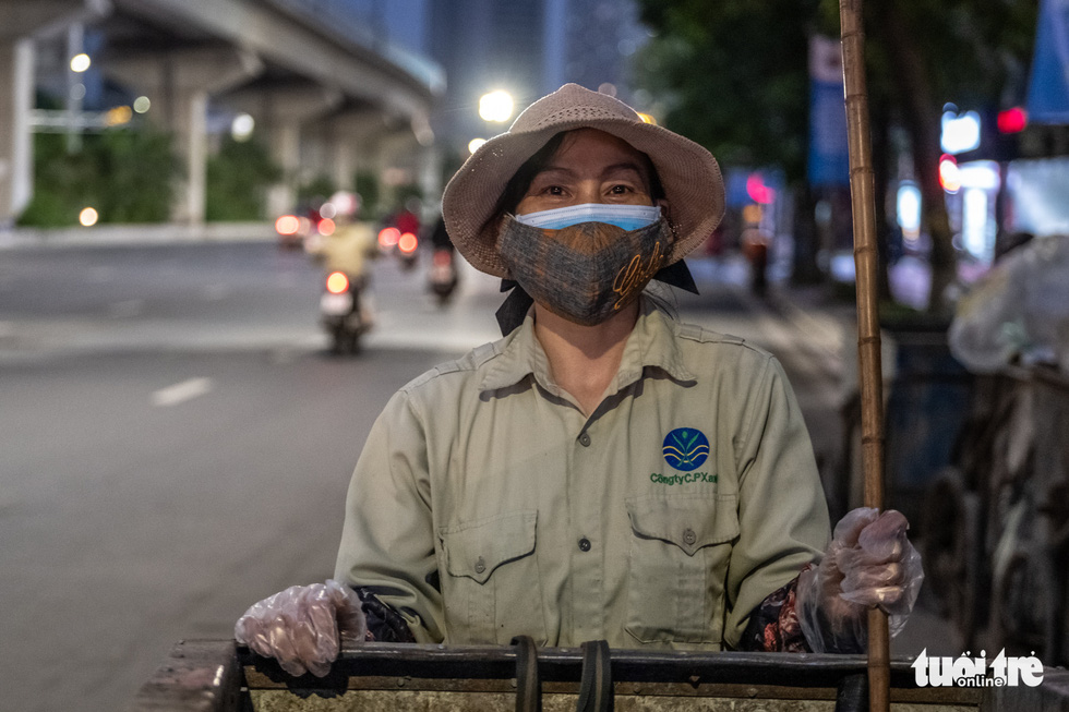 Pham Thi Bach, a sanitation worker works while wearing two face masks at the same time on a street in Hanoi, Vietnam. Photo: Nam Tran / Tuoi Tre