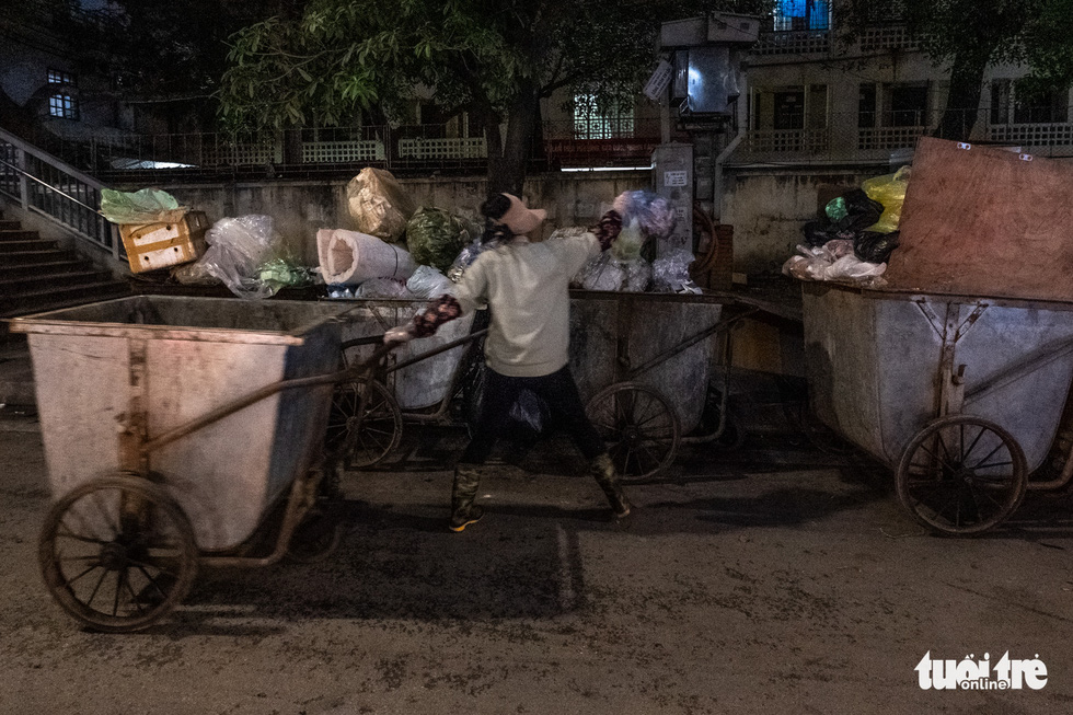 A female sanitation worker puts garbage into her trolleys on a street in Hanoi, Vietnam. Photo: Nam Tran/ Tuoi Tre