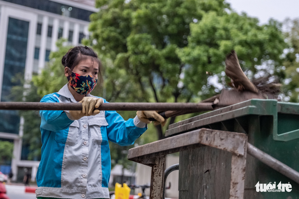 Tran Thi Huong, a sanitation worker from the Hanoi Urban Environment Companyworksg with her mask and gloves on in Hanoi, Vietnam. Photo: Nam Tran / Tuoi Tre