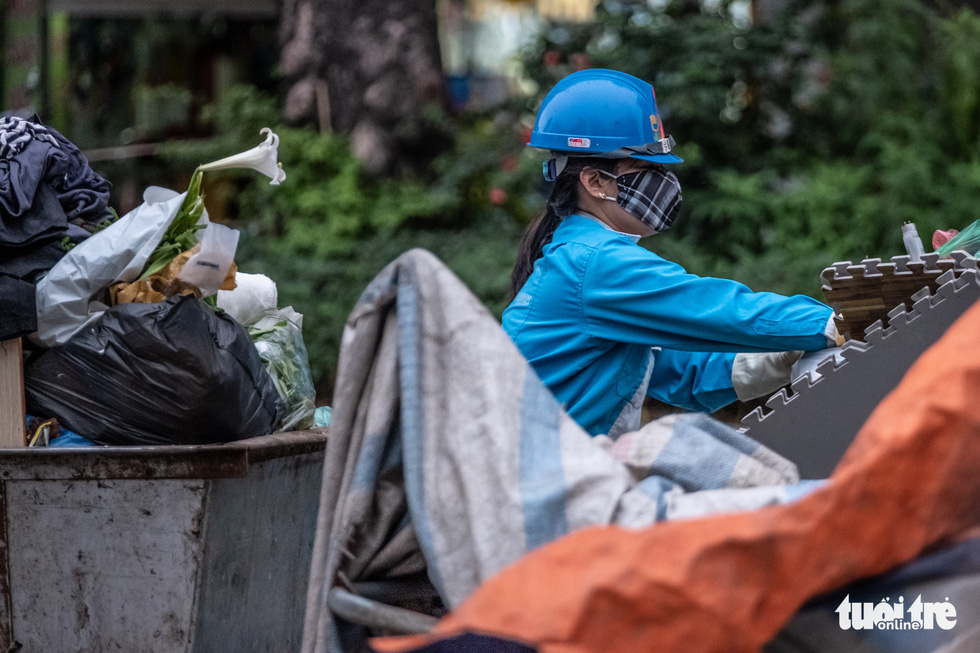 A female sanitation worker puts garbage into her trolleys on a street in Hanoi, Vietnam. Photo: Nam Tran / Tuoi Tre