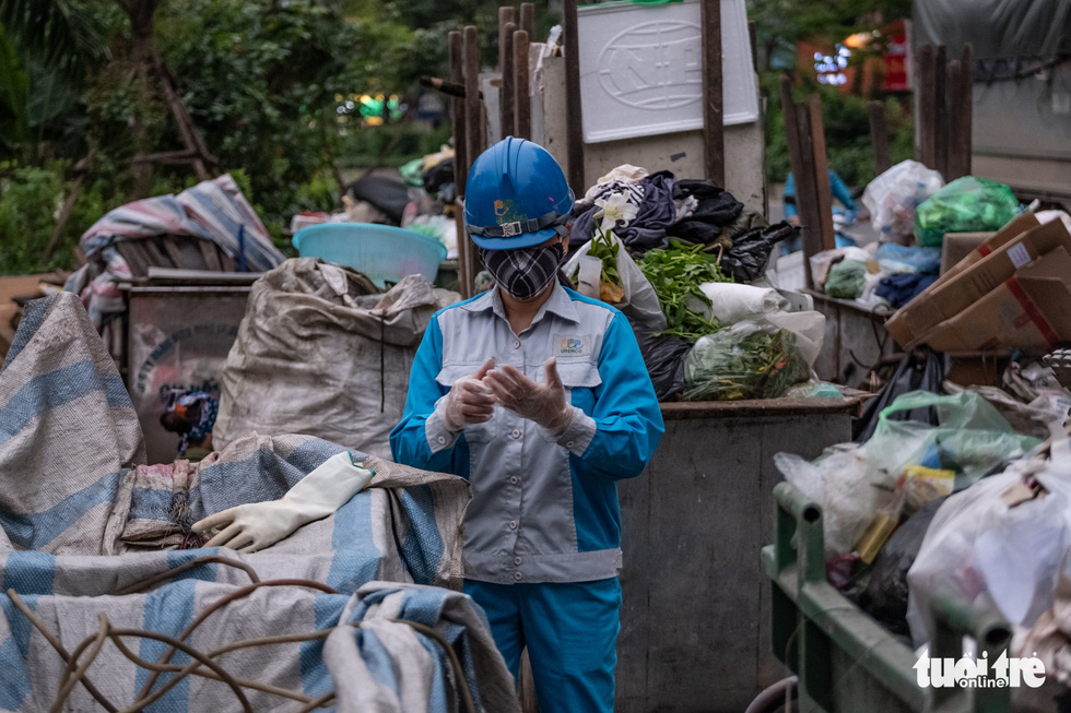A female sanitation worker in Hanoi, Vietnam prepares herself with protection gadgets before starting her working shift. Photo: Nam Tran / Tuoi Tre