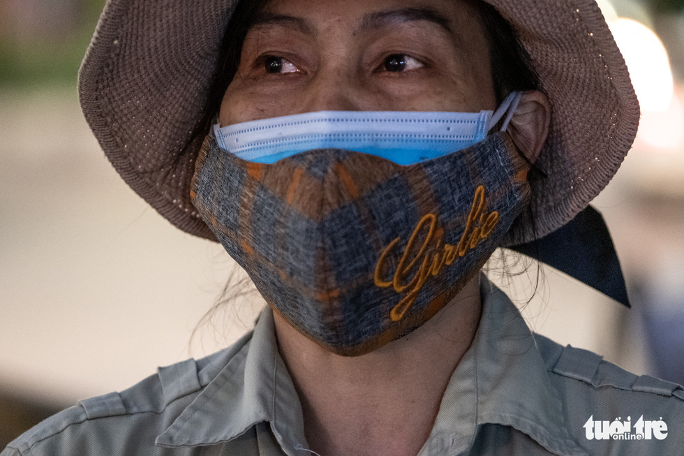 Pham Thi Bach, a sanitation worker in Hanoi, Vietnam, equips herself with a medical face mask inside a cloth mask while working. Photo: Nam Tran / Tuoi Tre