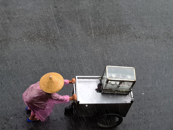 An old woman push street cart in the rain on a street in Binh Thanh District, Ho Chi Minh City. Photo: Ngoc Hien / Tuoi Tre