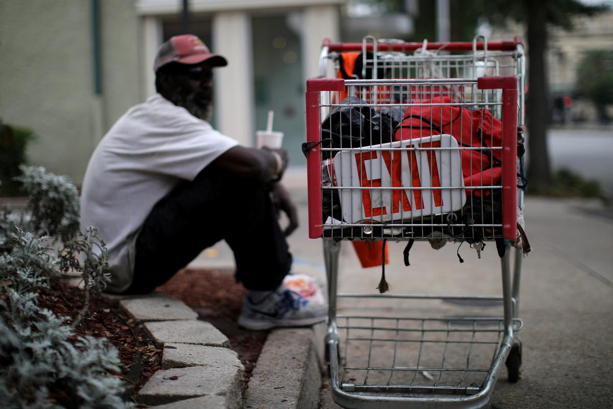A homeless man sits next to a shopping cart with a sign which reads 'Exit' as the spread of coronavirus disease (COVID-19) continues, in New Orleans, Louisiana U.S., April 8, 2020. Photo: Reuters