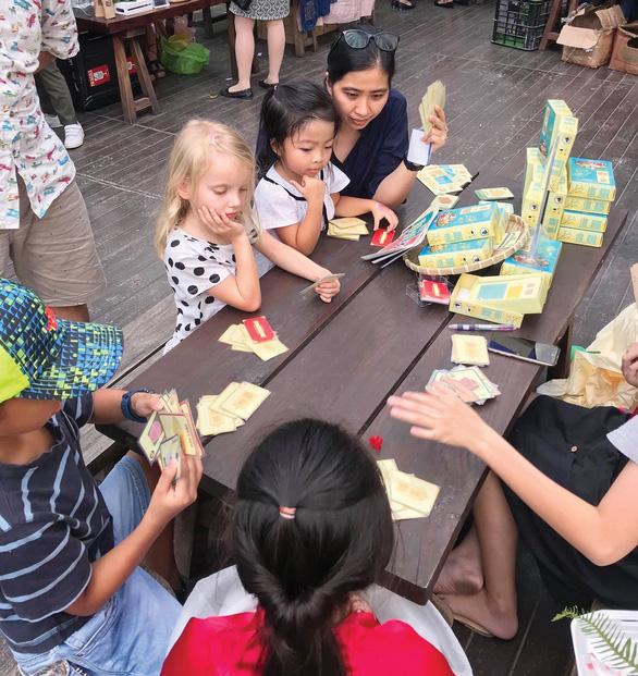 Children play 'Len Mam' board game at an event.