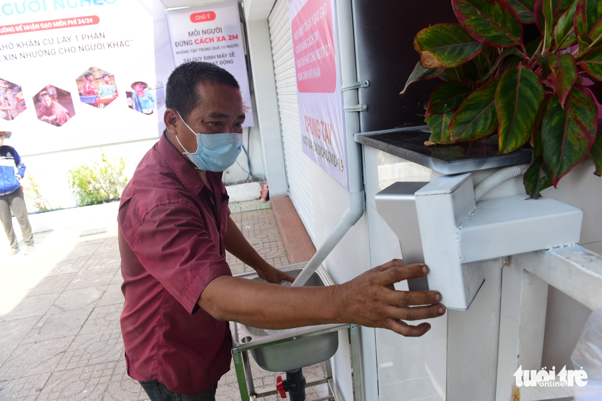 After pressing a button, rice flows from the rooftop down a chute and into a bag at a 'rice ATM' in Tan Phu District, Ho Chi Minh City, Vietnam. Photo: Quang Dinh / Tuoi Tre