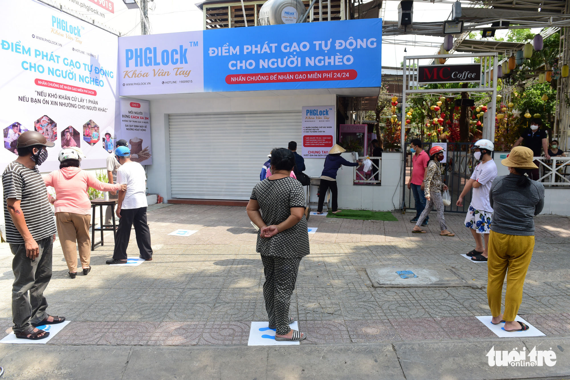 Those who wish to use the 'rice ATM' in Tan Phu District, Ho Chi Minh City, Vietnam must stand on labels placed two meters apart. Photo: Quang Dinh / Tuoi Tre