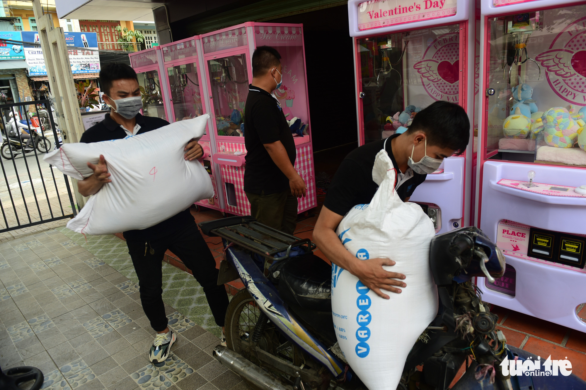 Neighbors donate rice to a 'rice ATM' in Tan Phu District, Ho Chi Minh City, Vietnam. Photo: Quang Dinh / Tuoi Tre