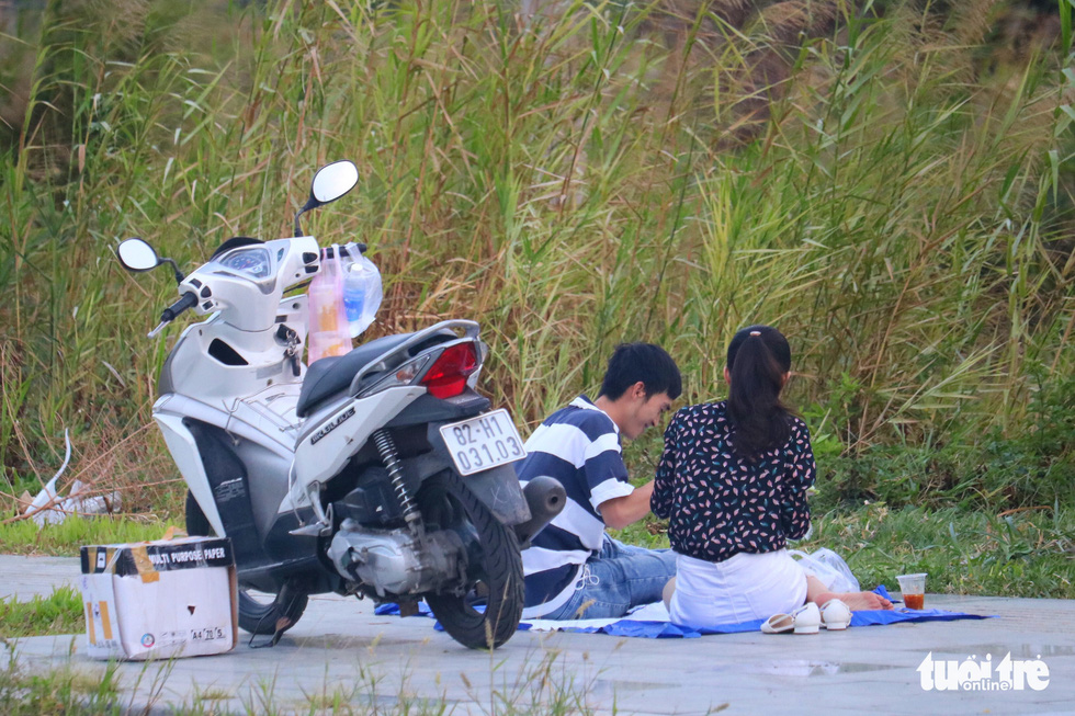 A couple has a picnic amid the COVID-19 pandemic at the kite field near oneend of Thu Thiem Bridge in District 2, Ho Chi Minh City, April 12, 2020. Photo: Ngoc Phuong / Tuoi Tre
