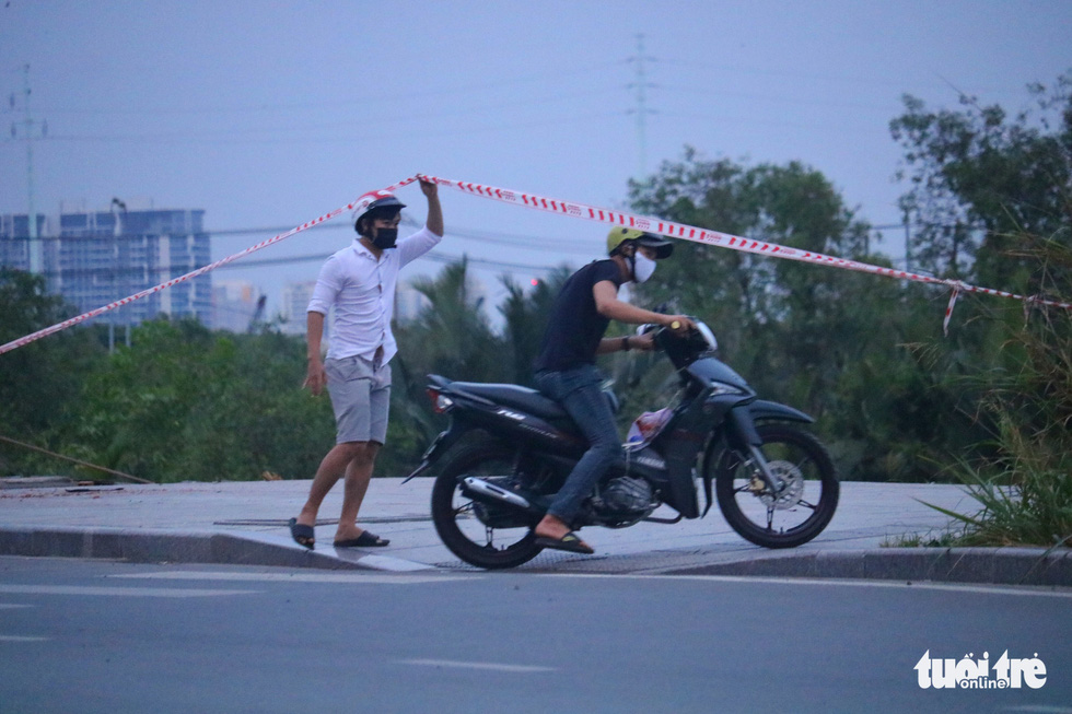 A man lifts a barricade tape for his friend to enter the kite field near oneend of Thu Thiem Bridge in District 2, Ho Chi Minh City, April 12, 2020. Photo: Ngoc Phuong / Tuoi Tre