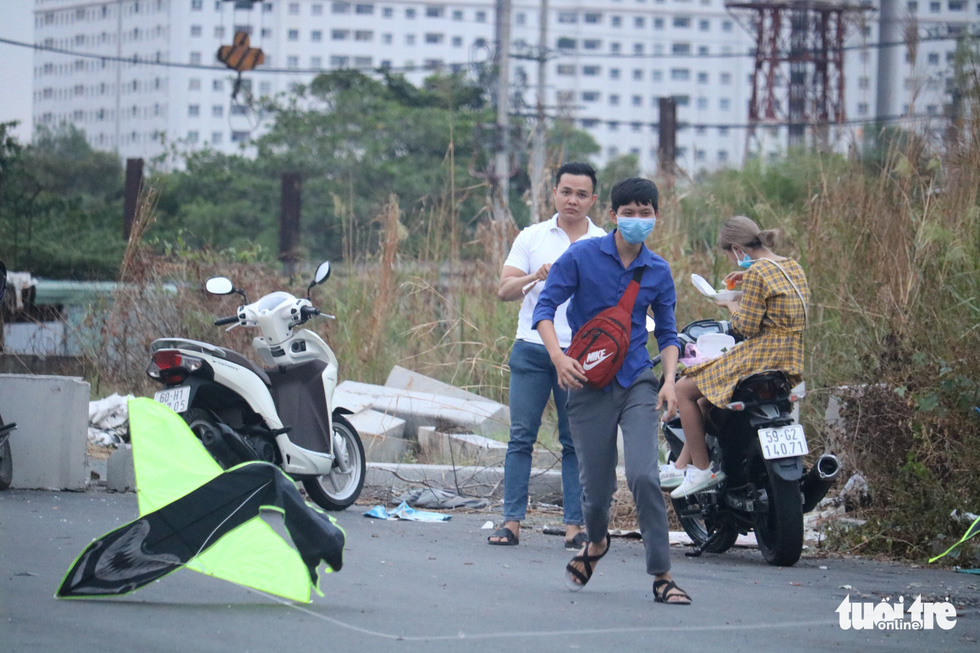 A man wears no face mask while going kite flying with his friends at the kite field near oneend of Thu Thiem Bridge in District 2, Ho Chi Minh City, April 12, 2020. Photo: Ngoc Phuong / Tuoi Tre