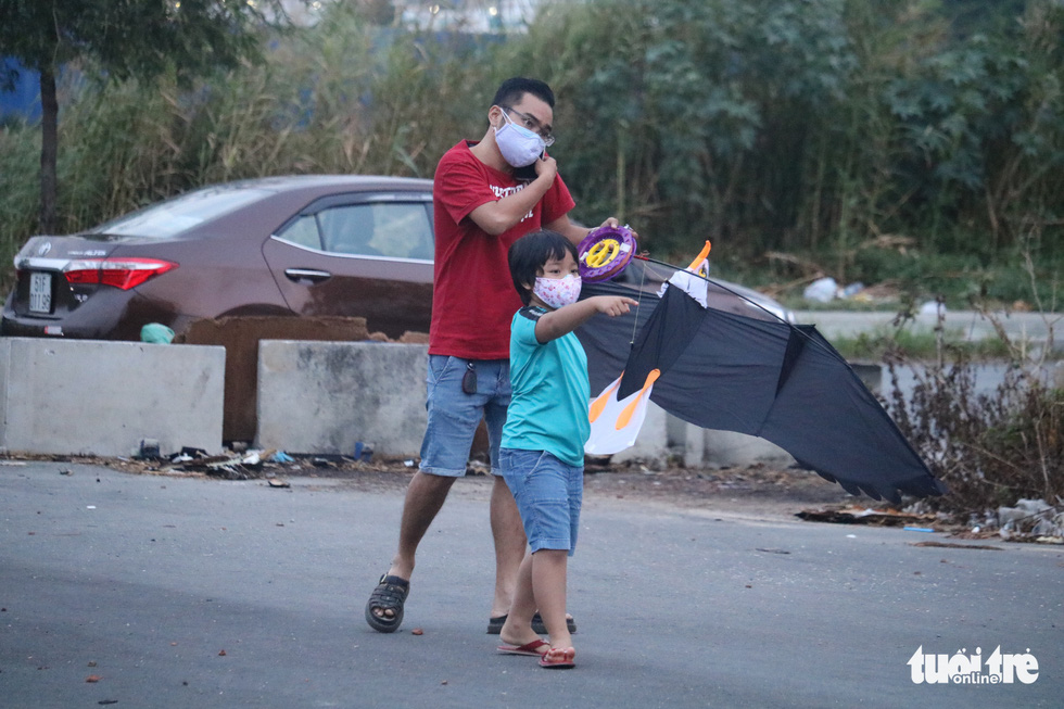 A father takes his son to go kite flying amid the COVID-19 pandemic at the kite field near oneend of Thu Thiem Bridge in District 2, Ho Chi Minh City, April 12, 2020. Photo: Ngoc Phuong / Tuoi Tre