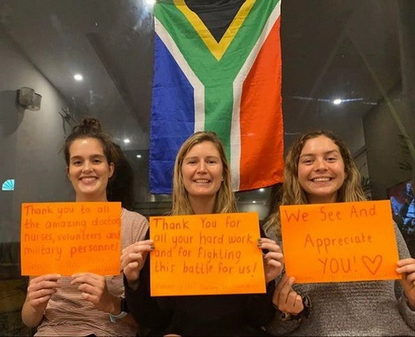 <em>From left: South Africa's Julia Meyer, Courtney Jordaan and Molly McMiles pose for a photo with their thank-you messages to Vietnam's frontline forces in the COVID-19 battle in this supplied picture.</em>