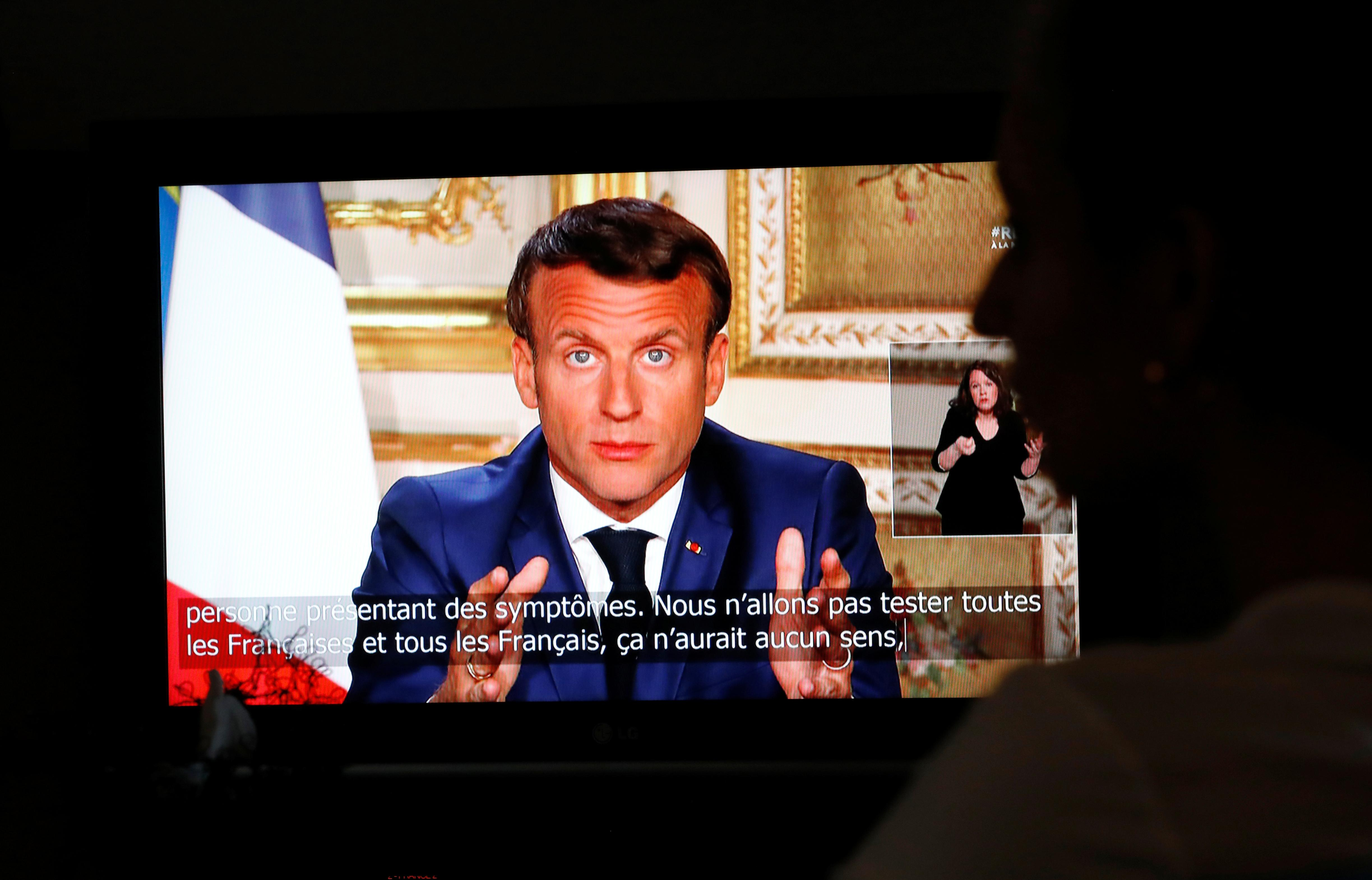 French President Emmanuel Macron is seen as he addresses the nation about the coronavirus disease (COVID-19) outbreak, on a television screen from confined people in Vertou, France, April 13, 2020. Photo: Reuters