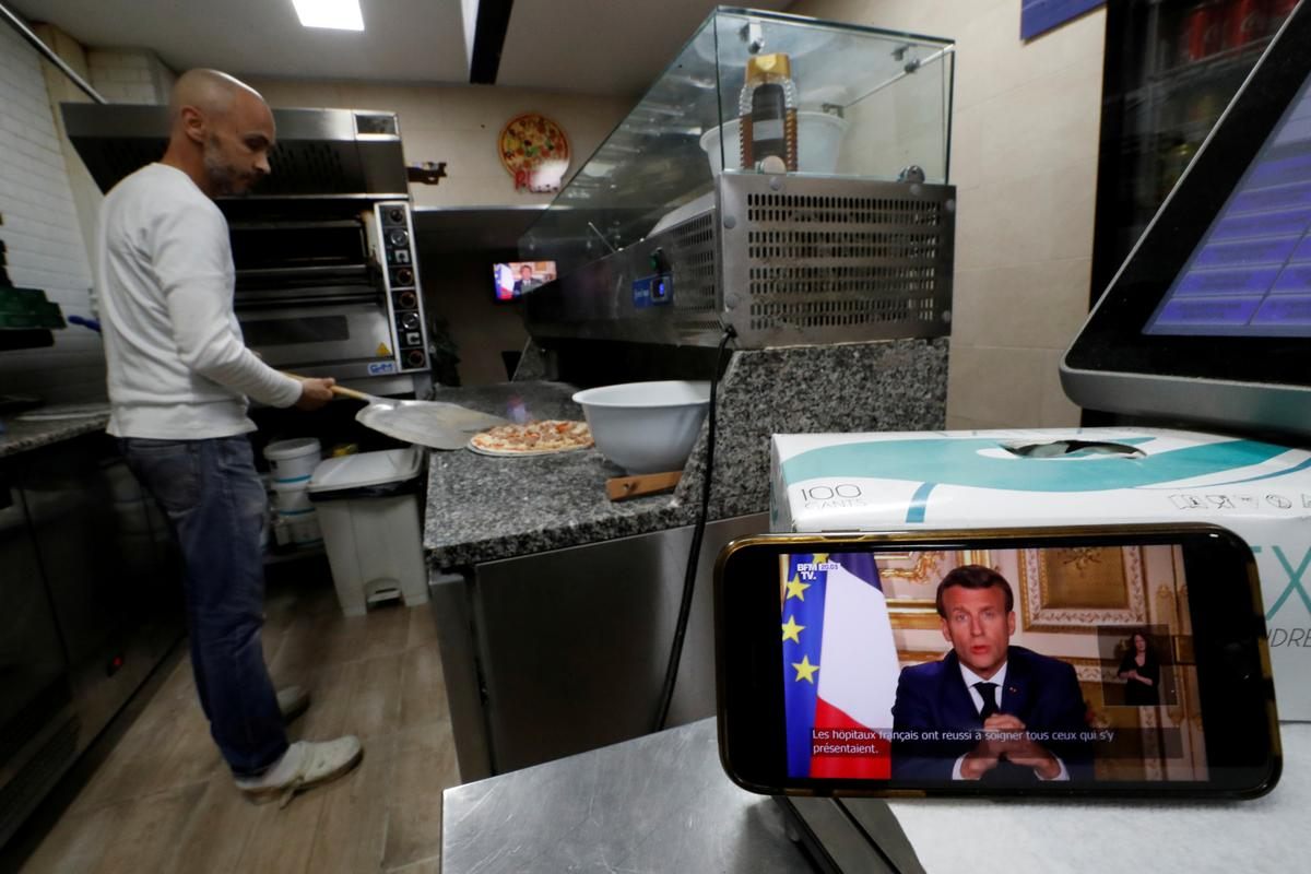 French President Emmanuel Macron is seen as he addresses the nation about the coronavirus disease (COVID-19) outbreak, on a television screen in a take away pizza shop in Nice, France, April 13, 2020. Photo: Reuters