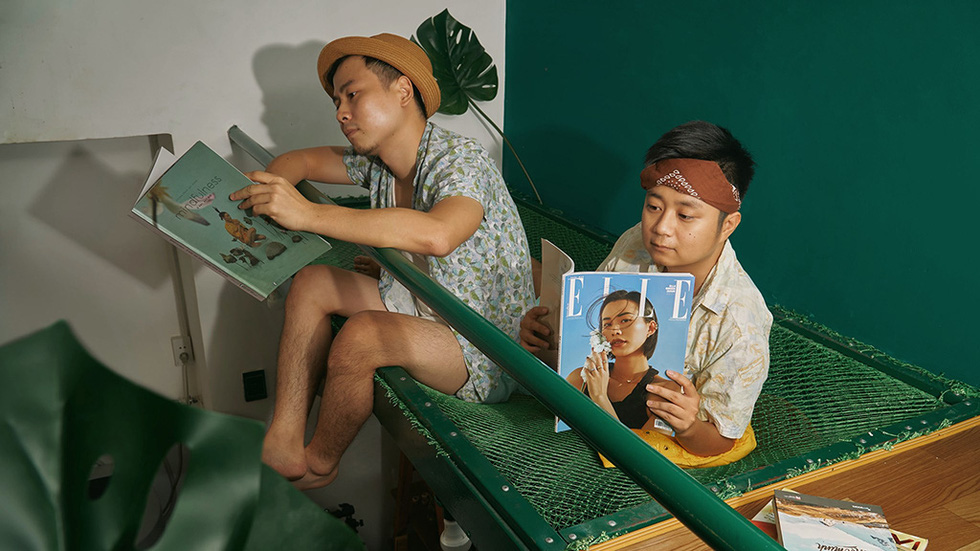 Trung Duc and Khai Quan read books while lying on a hammock in the middle of a forest in Indonesia's Bali in their imaginary 'Lost at Home' photo collection in which they staged their house into world scenes.