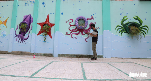 Art teacher Truong Hoang Thanh works on murals featuring ocean animals made from old car tires at Nui Thanh Elementary School in Da Nang City, Vietnam. Photo: D.C. / Tuoi Tre
