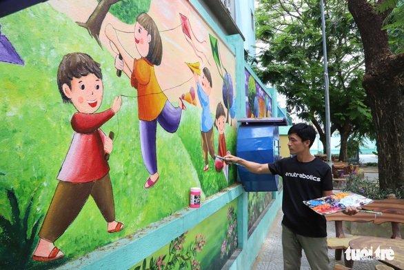 Art teacher Truong Hoang Thanh is seen finishing a mural in his 'Childhood Graden' series that features Vietnamese folk games at Nui Thanh Elementary School in Da Nang City, Vietnam. Photo: D.C. / Tuoi Tre