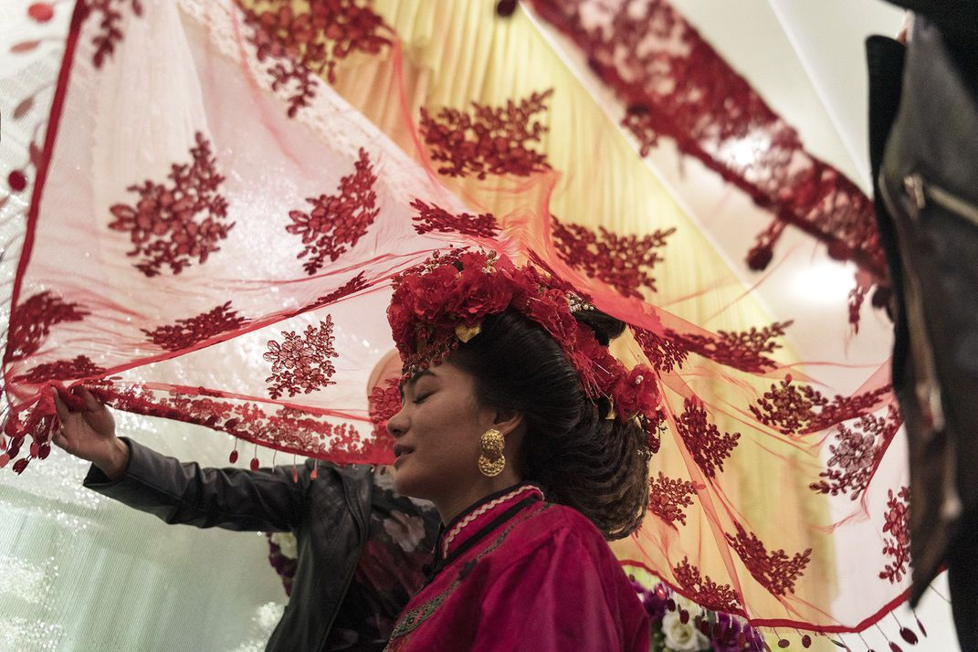 The photo 'Dungan wedding' by Yam G-Jun wins the People award of the 17th annual Smithsonian magazine photo contest. In the photo, Madina, 20, an ethnic Dungan, is covered by a red veil before she leaves for the groom's house during wedding ceremony in Milyanfan, Kyrgyzstan. Dungans wear traditional Chinese-influenced wedding gowns, follow traditional Hui Chinese wedding ceremonies from the 19th century and practice endogamy, but due to shrinking population size, they have stopped the practice and allowed Dungans to marry other ethnicities.