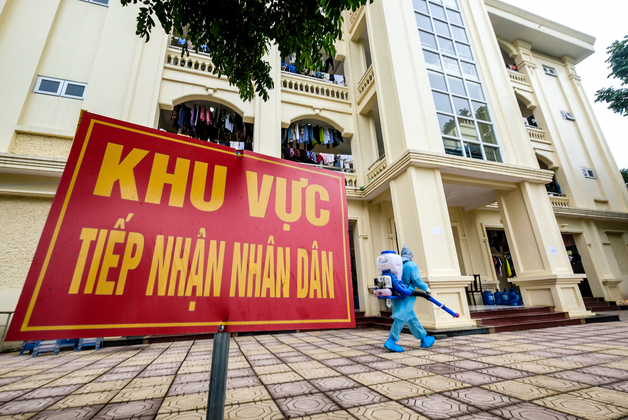 A soldier in protective gear disinfects a three-floor building used to isolate people returning from South Korea at a COVID-19 quarantine facility in Hanoi, Vietnam. Photo: Nam Tran / Tuoi Tre