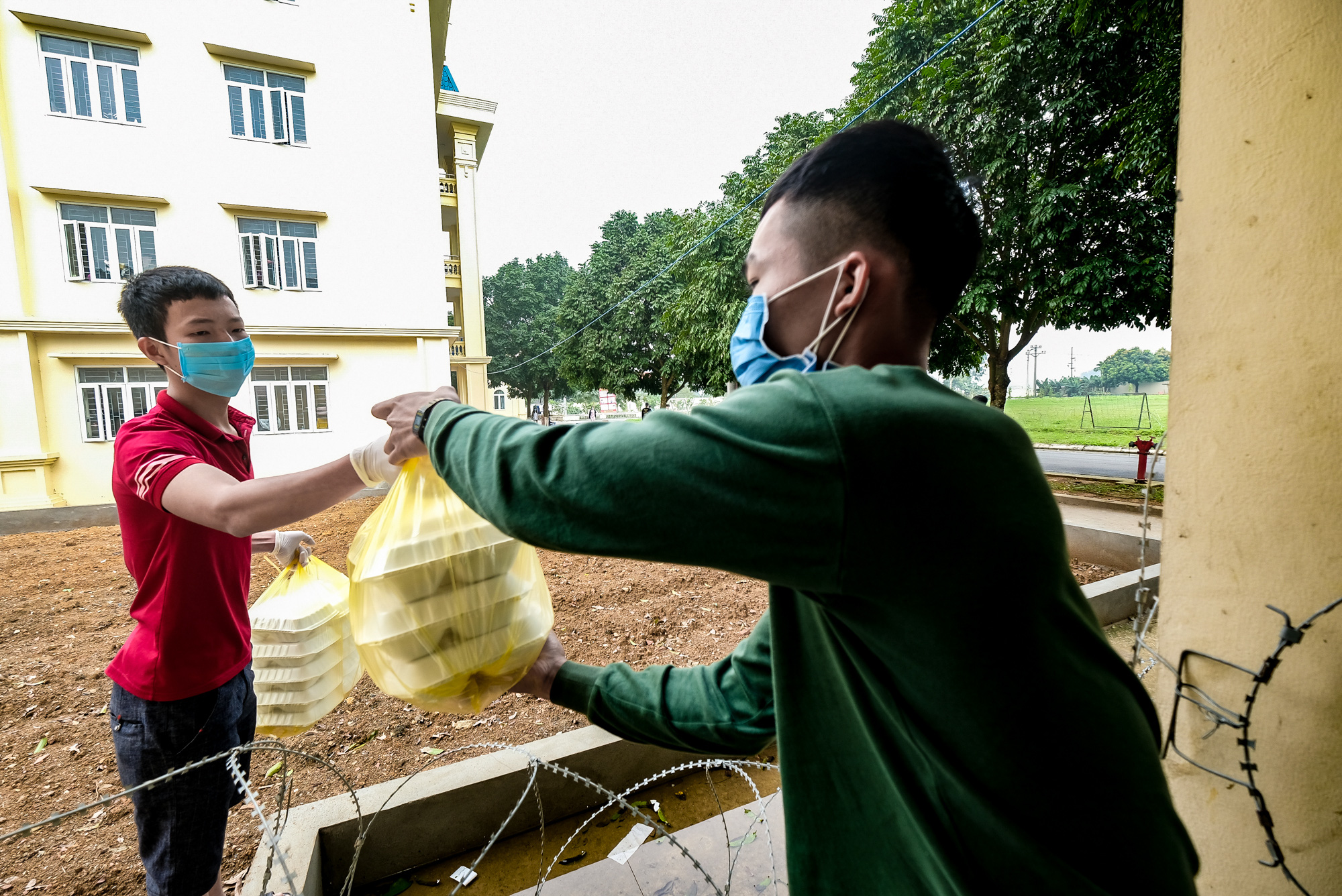 A soldier hands prepared meals to a person in isolation at a COVID-19 quarantine facility in Hanoi, Vietnam. Photo: Nam Tran / Tuoi Tre