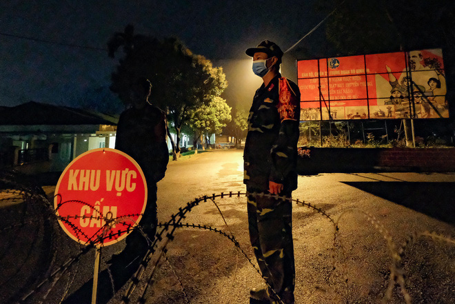 At night, military personnel get out of their blue protective gear and brave cold weather to take turns guarding a COVID-19 quarantine facility in Hanoi, Vietnam. Photo: Nam Tran / Tuoi Tre