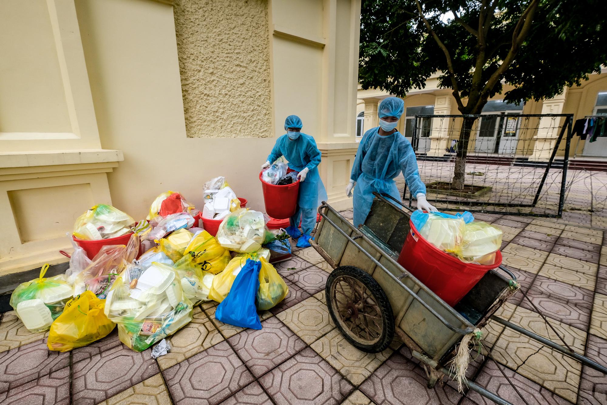 Military personnel in protective gear dispose of garbage at a COVID-19 quarantine facility in Hanoi, Vietnam. Photo: Nam Tran / Tuoi Tre