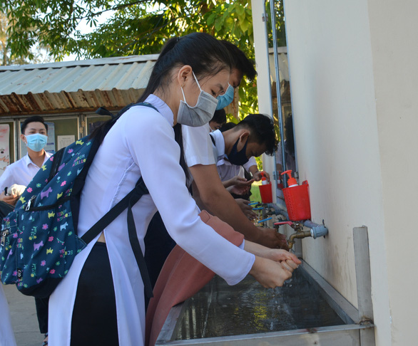 High school students wash their hands before entering the classroom on their first day at school after a three-month COVID-19 break in Ca Mau Province, Vietnam, April 20, 2020. Photo: Nguyen Hung / Tuoi Tre