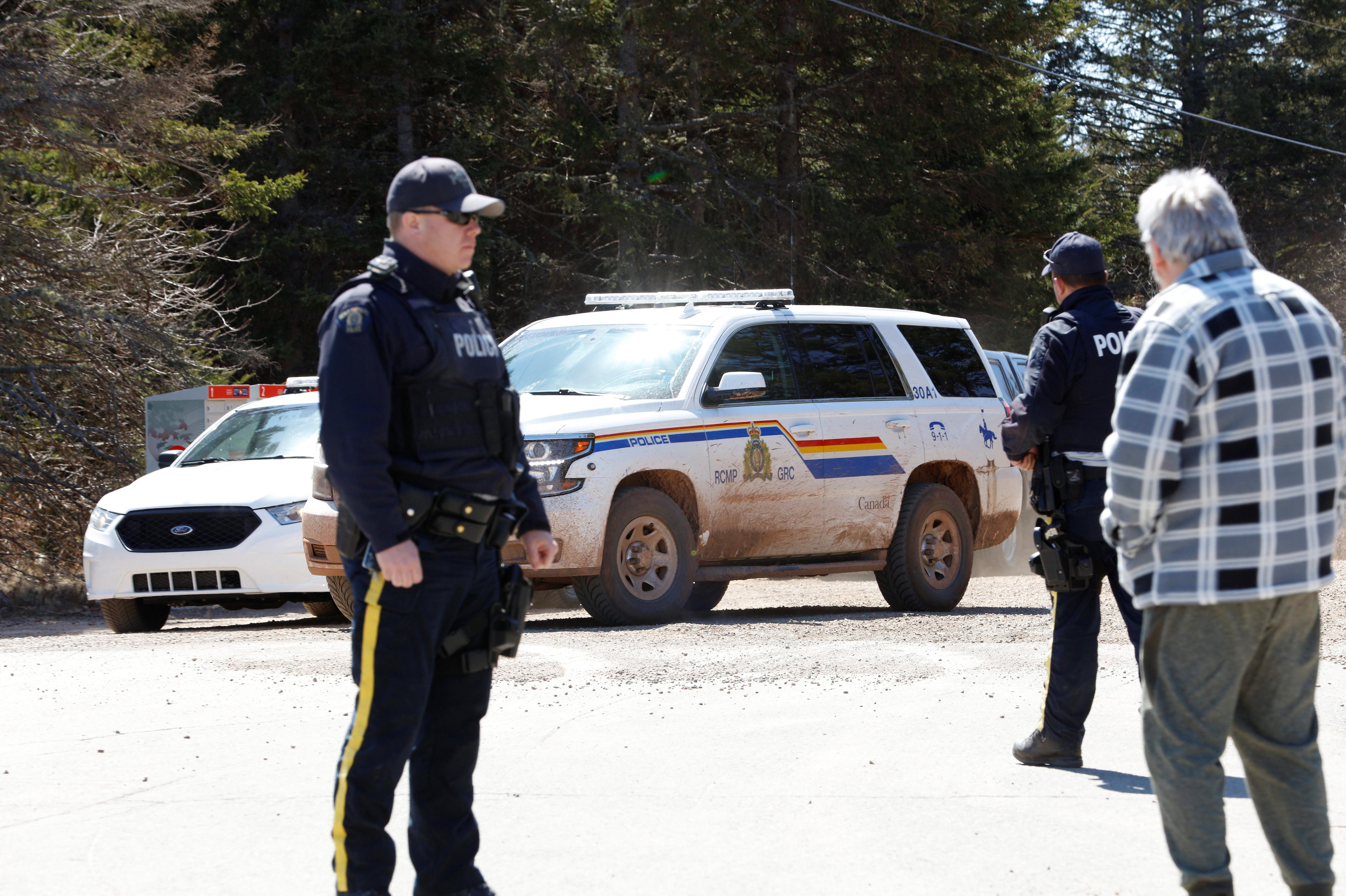 A Royal Canadian Mounted Police (RCMP) SUV pulls up to the end of Portapique Beach Road while an officer speaks with a man after the police finished their search for Gabriel Wortman, who they describe as a shooter of multiple victims, in Portapique, Nova Scotia, Canada April 19, 2020. Photo: Reuters