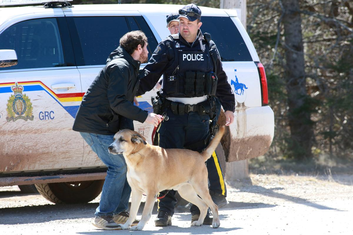 A Royal Canadian Mounted Police (RCMP) officer returns a dog to an individual since the road is shut down after a manhunt for Gabriel Wortman, who they describe as a shooter of multiple victims, in Portapique, Nova Scotia, Canada April 19, 2020. Photo: Reuters