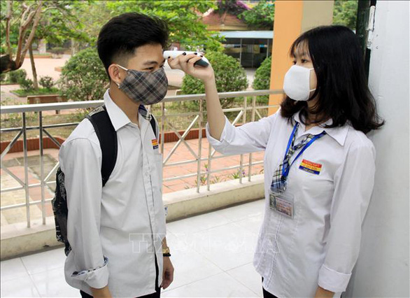 A high school student has his body temperature checked on his first day at school after a three-month COVID-19 break in Thai Binh Province, Vietnam, April 20, 2020. Photo: Vietnam News Agency