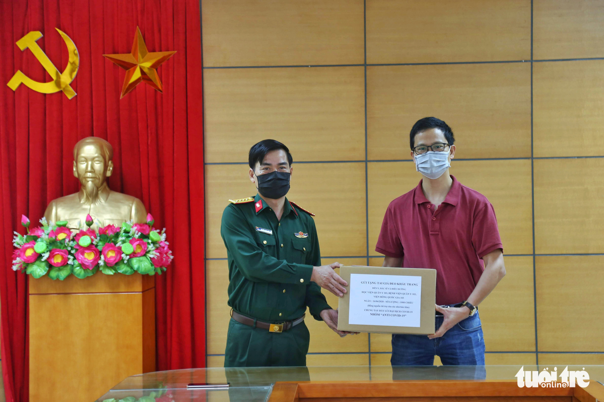 Phan Manh Ha (right), representing the volunteer Anti COVID-19 group, presents 1,000 ears guards to doctors at 103 Military Hospital and the National Institute of Burns in Hanoi, Vietnam, April 16, 2020. Photo: Mai Thuong / Tuoi Tre