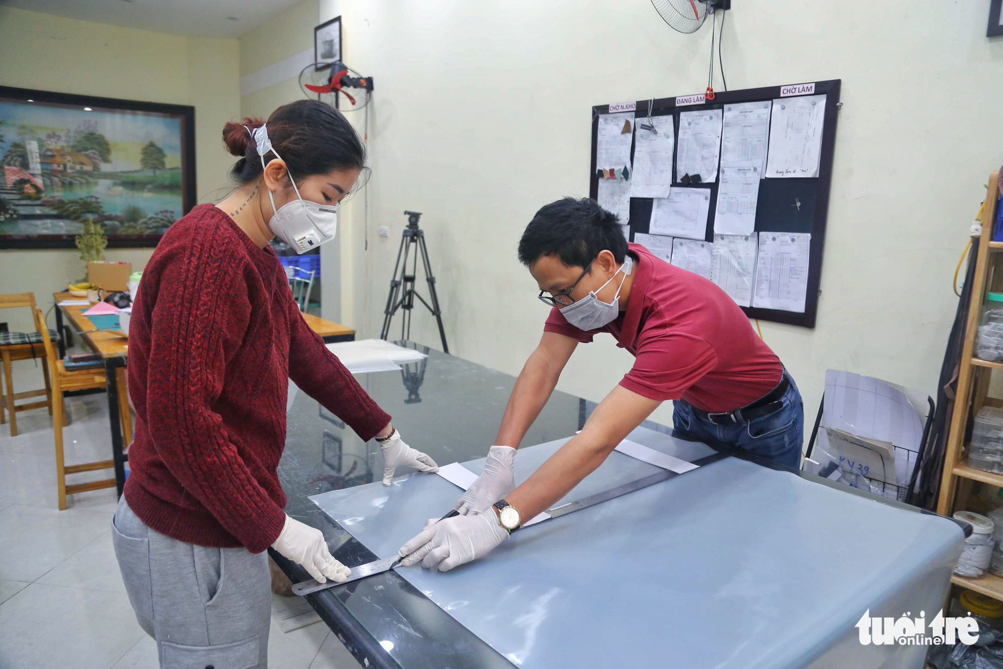 Two members of a volunteer group in Hanoi, Vietnam cut a silicon sheet into small pieces to be made into ear guards. Photo: Mai Thuong / Tuoi Tre